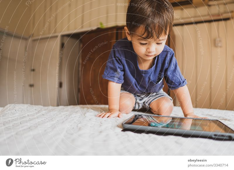 cute young mixed race boy playing with an electronic device Joy Happy Playing Reading Summer Garden Bedroom Child Computer Technology Internet Human being