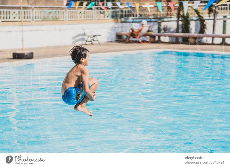 young asina boy jumping into the swimming pool Joy Happy Face Relaxation Swimming pool Leisure and hobbies Playing Vacation & Travel Summer Sports Success Child