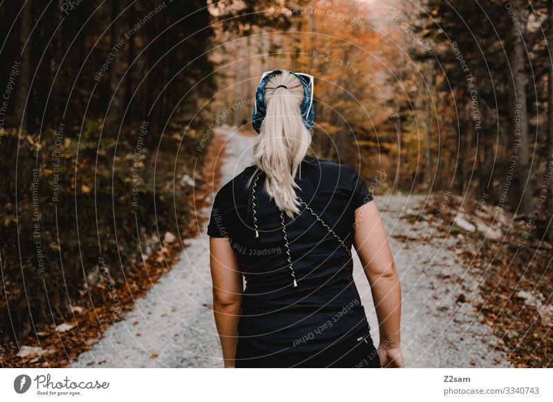 Ascent to the mountain crusher tip Hiking economic path ascent Forest Autumn Going back view Young woman Blonde Braids Athletic foliage T-shirt