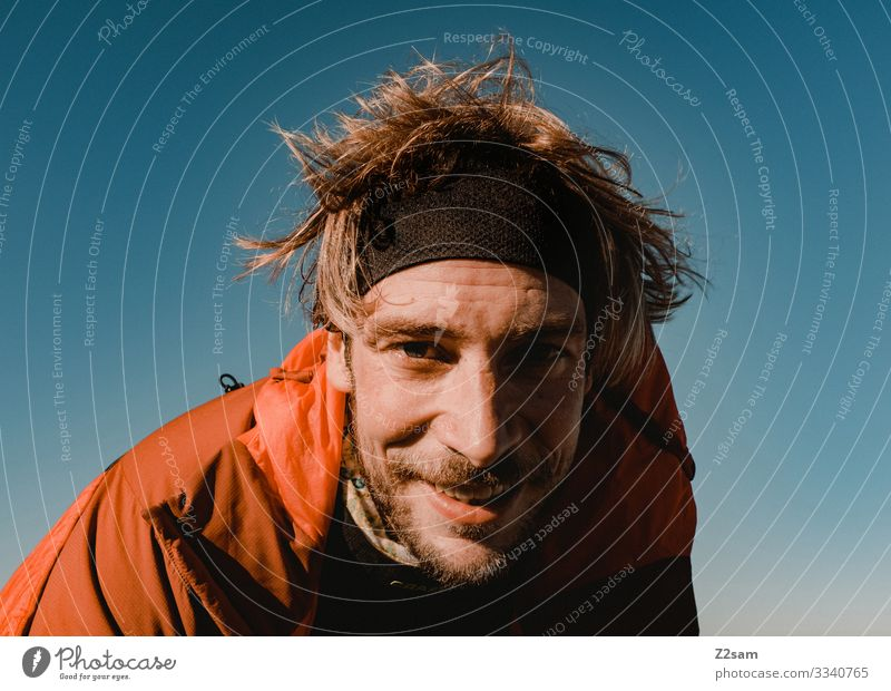 Portrait of a young hiker crusher tip sharpened Hiking Man Nature Peak portrait Athletic Face Facial hair Headband warm Sun Blue sky Landscape