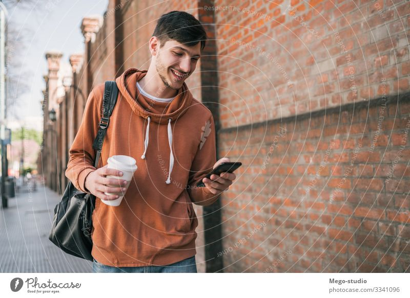 Man using his mobile phone. Lifestyle Style Joy Happy Contentment Telephone PDA Technology Human being Adults Hand 1 18 - 30 years Youth (Young adults) Street