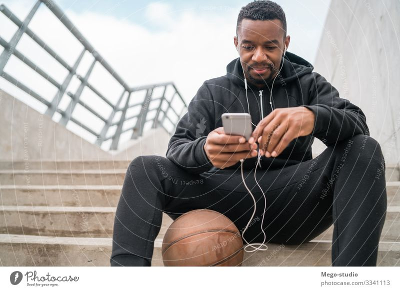 Athletic man using his mobile phone. Lifestyle Leisure and hobbies Sports Telephone PDA Technology Human being Man Adults 1 30 - 45 years Fitness To enjoy