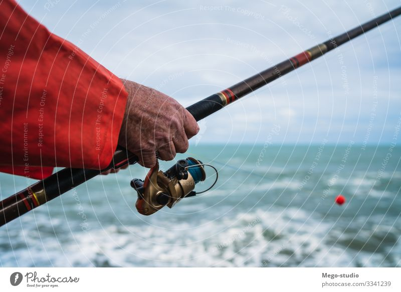 Fisherman fishing at the sea. Lifestyle Happy Relaxation Leisure and hobbies Playing Vacation & Travel Ocean Sports Retirement Human being Man Adults Hand 1
