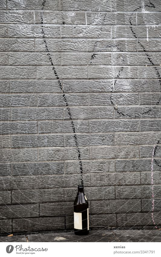 Beer bottle on the wall Beverage Alcoholic drinks Bottle Town Wall (barrier) Wall (building) Facade Characters Graffiti Dirty Trashy Brown Gray Black