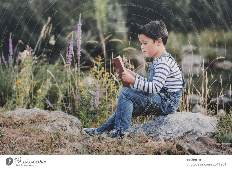 Child sitting reading a book in the field Lifestyle Leisure and hobbies Reading Summer Study Human being Masculine Boy (child) Infancy 1 8 - 13 years Book