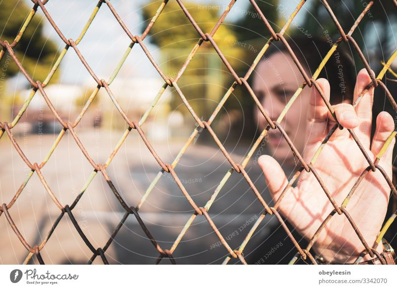 woman stading beohind a faence feeling trapped and alone Beautiful Woman Adults Environment Think Loneliness Considerate tranquil outdoor scene early morning