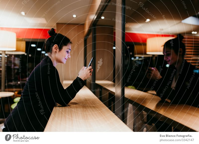 young woman using mobile phone in a cafe or restaurant indoors. Technology and lifestyle Woman Cellphone Interior shot Restaurant Café Window Businesswoman
