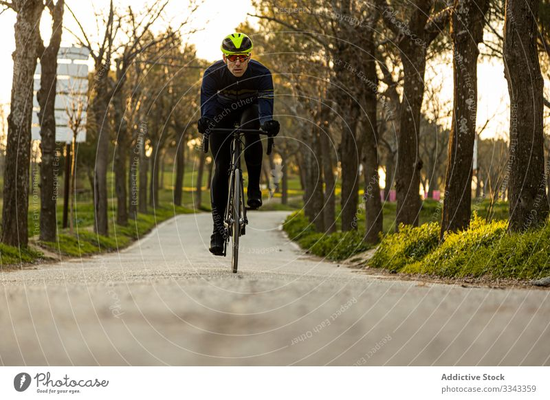 Man cycling in a park race freedom helmet ride speed bicycle bike cyclist exercise fast fitness man person sport adventure healthy lifestyle nature road urban