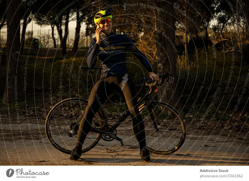Man cycling in a park using mobile phone freedom helmet ride bicycle bike cyclist exercise fitness man person sport adventure healthy lifestyle nature road