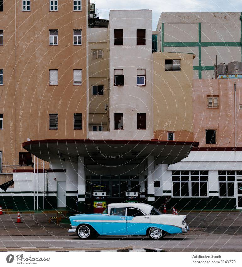 Stylish rare blue car on city street gas station road asphalt building exterior vintage retro design urban transport vehicle district lifestyle tourism