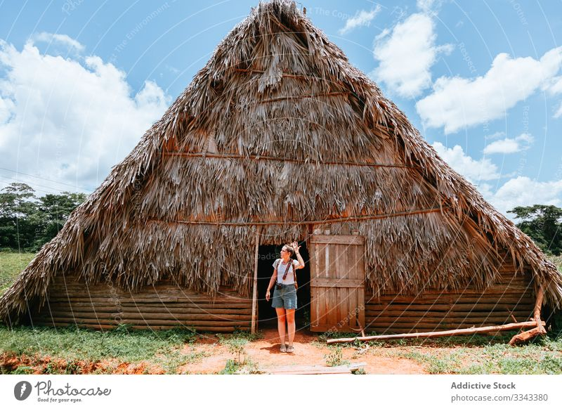 Woman on vacation near old house at countryside woman rural doorway standing thatched roof blue sky summer cloud green grass travel tourism nature young female