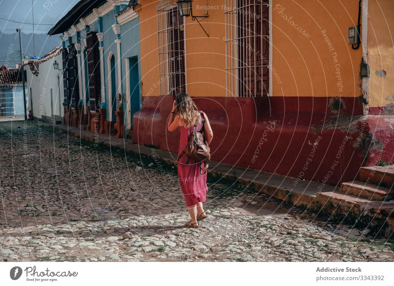 Anonymous female tourist with backpack at city street woman tourism walking stroll dress gown architecture exterior explore cuba travel vacation holiday