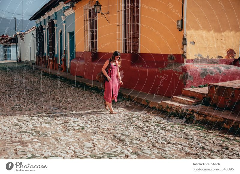 Female tourist with backpack at city street woman tourism walking stroll dress gown architecture exterior explore female cuba travel vacation holiday lifestyle