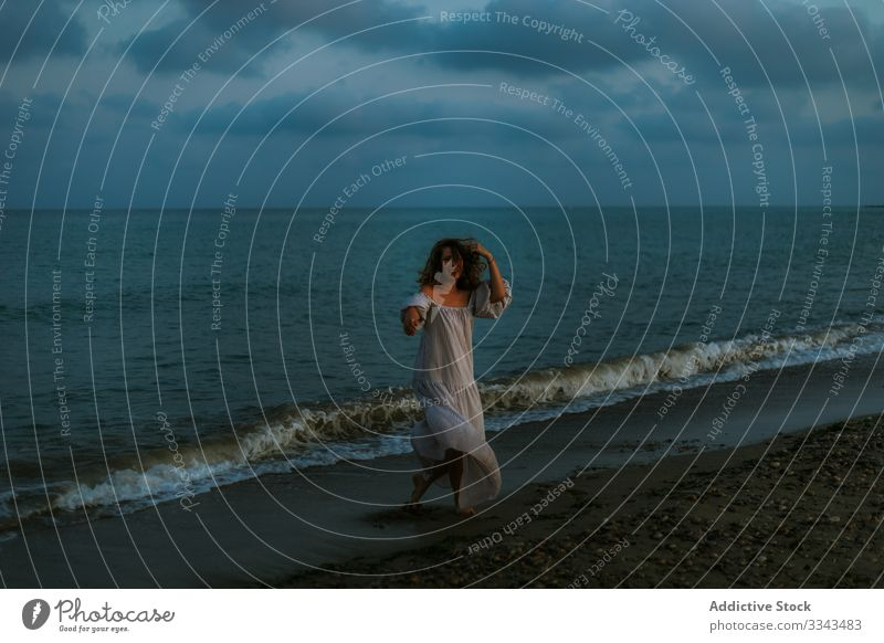 Female tourist seaside woman beach waves barefoot seashore sky heaven dusk clouds female lady walking coastline empty lonely blue dress beautiful vacation water