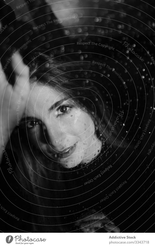 Woman smiling at camera through glass woman raindrop touch alone solitude window wet daydream rainy contemplation farewell vision charming goodbye female relax