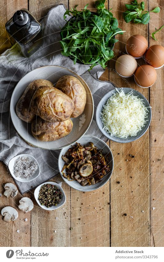 Tasty dish of potatoes and fresh ingredients on table stuffed filled rustic wooden homemade green herb spice fried mushrooms eggs grated cheese salt olive oil