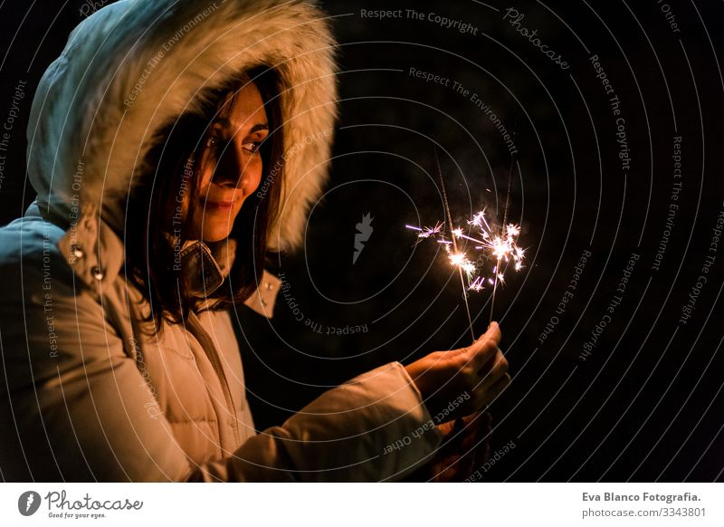 beautiful young woman hoding a sparkle at night, having fun and smiling Party Night Light Joy Dark Fire firework Hand Flame sparkles Bright Lifestyle