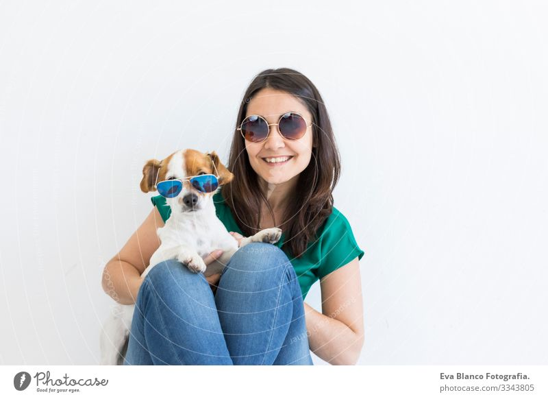 Beautiful young woman playing with her little cute dog at home. Lifestyle portrait. Love for animals concept. white background. Both wearing sunglasses Dog Home