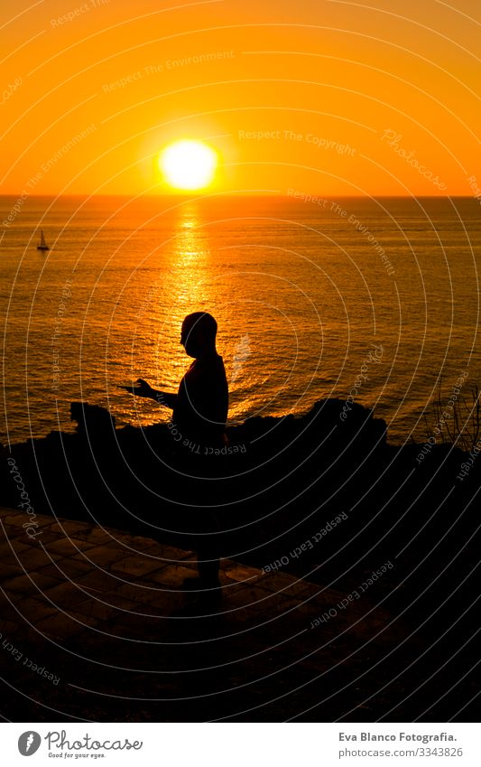 silhouette of a young man using mobile phone at sunset. Ocean background. Vacation and technology concept Youth (Young adults) Hand Solar cell Telephone