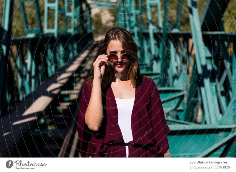 portrait of a young beautiful woman on a green bridge. Wearing stylish clothes. Holding sunglasses. LIfestyle. Outdoors. Sunny Railroad Woman pretty