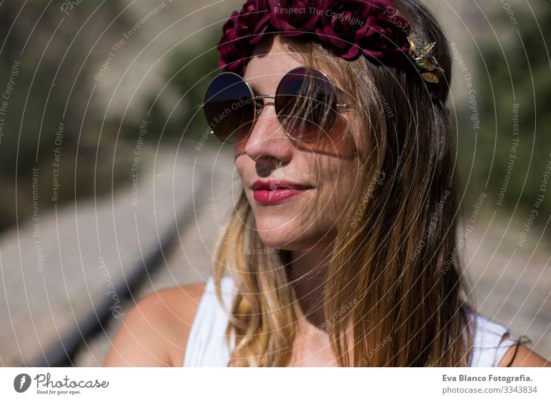 close up portrait of a young beautiful woman wearing modern sunglasses and a red roses wreath on her head. Outdoors. Sunny. Lifestyle Freedom Beauty Photography