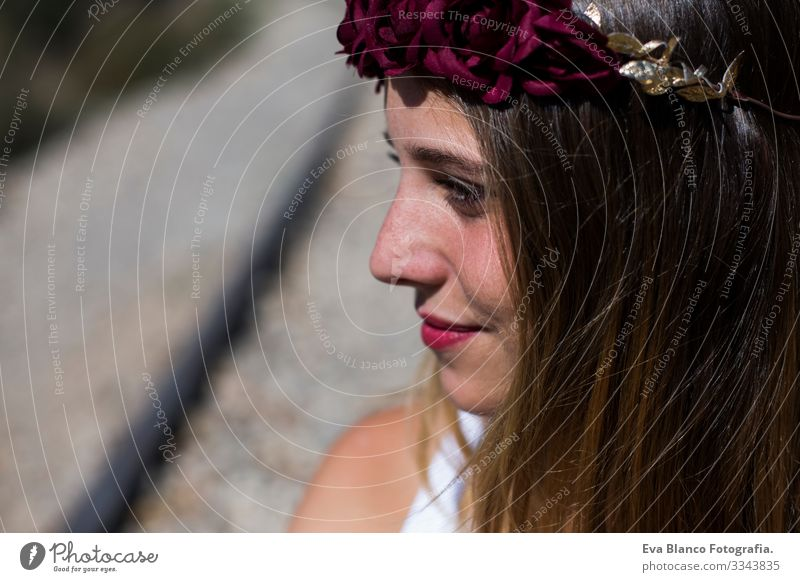 Profile face Portrait Beautiful young woman with a red roses wreath on her head. Red lips. Outdoors. Sunny. Railway. Lifestyle Freedom Beauty Photography