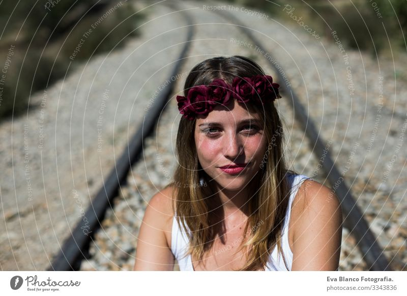 portrait of a young beautiful woman wearing a red roses wreath on her head and looking at the camera.Sitting on a railway. Outdoors. Sunny. Lifestyle Freedom