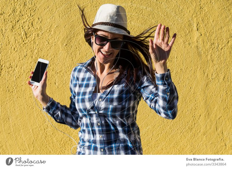 happy beautiful young woman listening to music and having fun over yellow background. She is wearing hat and modern sunglasses. lifestyle Portrait photograph