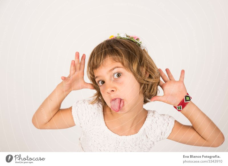 Little girl with funny face tongue outside on white background Portrait photograph Joy Child Cute lifestyle happiness Cheerful Beautiful Small Hair