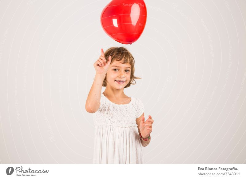 kid playing with a red balloon in the studio. Fun, lifestyle. white background Portrait photograph Joy Child Cute lifestyle happiness Cheerful Beautiful Small