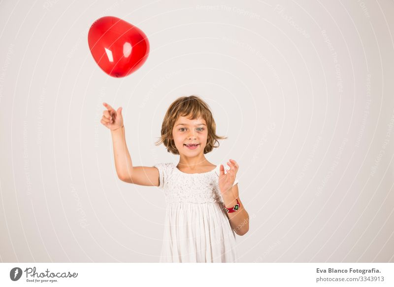 kid playing with a red balloon in the studio. Fun, lifestyle, white background Portrait photograph Joy Child Cute lifestyle happiness Cheerful Beautiful Small