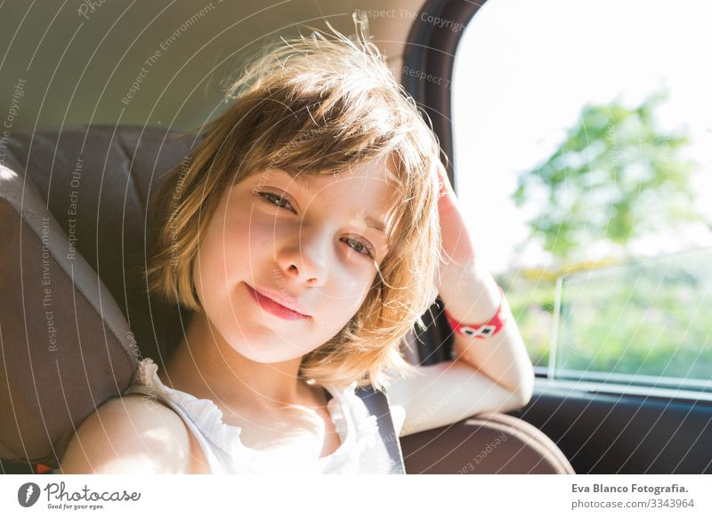 cute small child, blonde girl, in car seat wearing seat belts happy is going to go in the path of the road, sun glare reflected Belt Summer Small Child