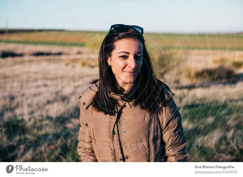 outdoors portrait of a young beautiful woman at sunset. Autumn or winter season. She is wearing a brown coat. Lifestyle Winter hispanic Fashion