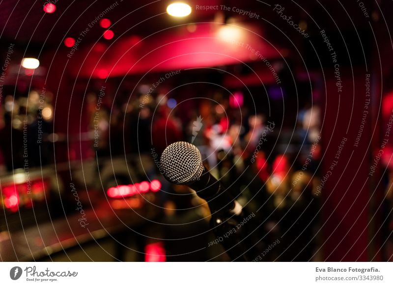 microphone on a stand up comedy stage with colorful bokeh , high contrast image. Microphone Party Night Club Human being crowd Christmas & Advent Red