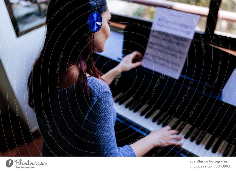young woman holding playing piano by reading a music sheet. Music concept indoors. Back view Style Human being Key note Lessons Caucasian Press Chord Woman