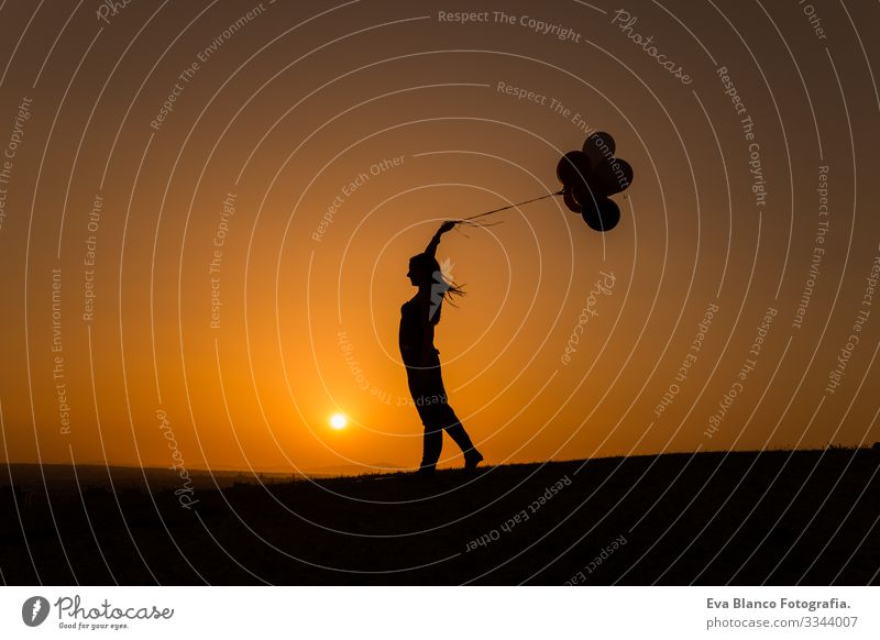 silhouette of a young woman playing with balloons at sunset Summer Sunset Love Joy Nature Silhouette Youth (Young adults) Woman Freedom Lifestyle Sky Relaxation
