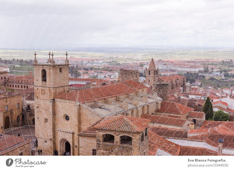 Aerial views of the beautiful city of Caceres, Spain. Stone fortress town. Cathedral in front. Cloudy sky Catholicism historical Statue medieval Church Deserted
