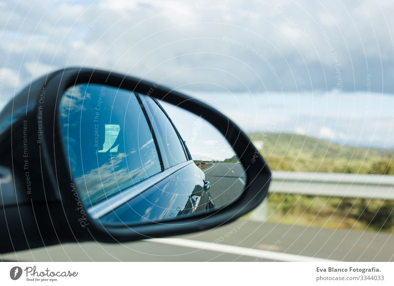 car on the road with motion blur background and rear view mirror. Travel concept. Cloudy sky Speed Blur Bright Mirror Street Modern Future Power Wheel Movement