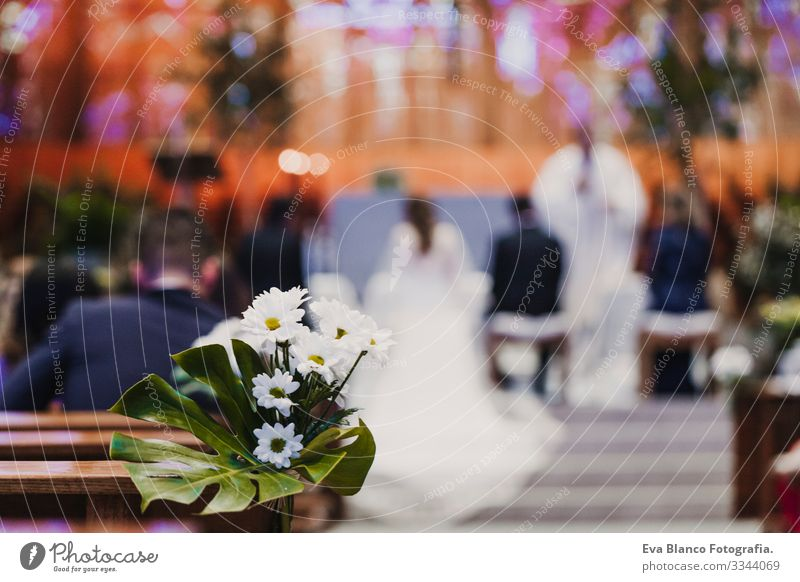 Beautiful flower wedding decoration in a church. Selective focus. Unrecognizable blurred Groom and bride on background. Marriage concept in church bunch White