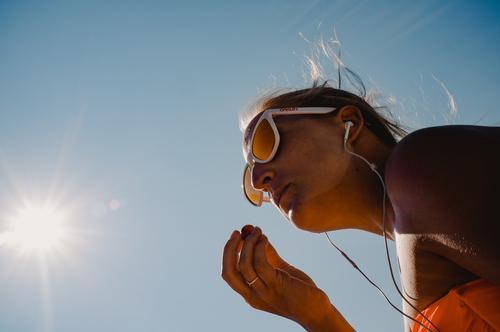 Eating grapes on the beach Lake Garda Break Beach Relaxation Listen to music Headphones sunglasses Blonde Girl Woman youthful hip Beautiful Bikini Sun Summer
