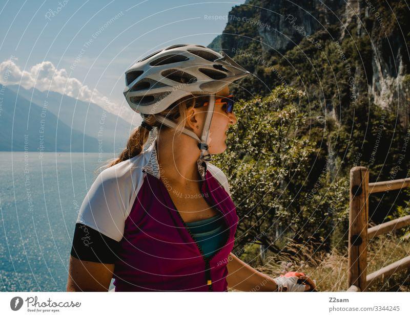 Mountain biker at Lake Garda alpine crossing mtb transalp panorama Sportsperson Athletic Braids Blonde Helmet Safety Protection Vantage point cliffs ponal