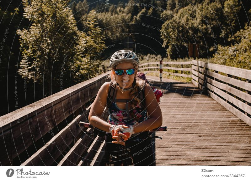Young woman with the mountain bike in Italy alpine crossing Lake Garda Mountain bike mtb transalp Laughter Helmet Sunglasses Cycle path Summer Sports Nature