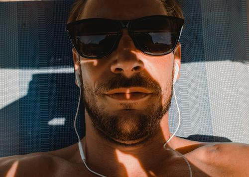 Chilling and listening to music on holiday Headphones Lie vacation Facial hair Man Young man Couch sunglasses Summer Summer vacation sun lounger portrait