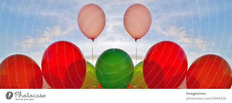 Balloons background and sun of the blue sky shining through clouds. decorative balloons in the blue sky. concept of love and Valentine's Day, wedding. outdoor party decoration