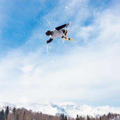 Free style skier. Lifestyle Joy Relaxation Adventure Winter Snow Mountain Sports Nature Park Alps Movement Jump Speed Blue White Brave Safety Dangerous Skier