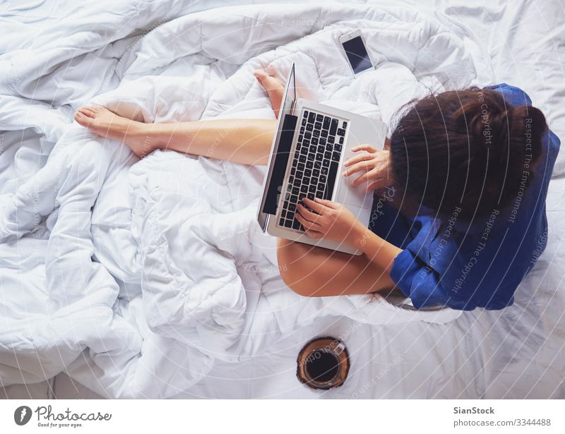 Young woman drinking coffee at home in her bed, top view Coffee Beautiful Life Relaxation Reading Bedroom Work and employment Workplace Computer Notebook Woman