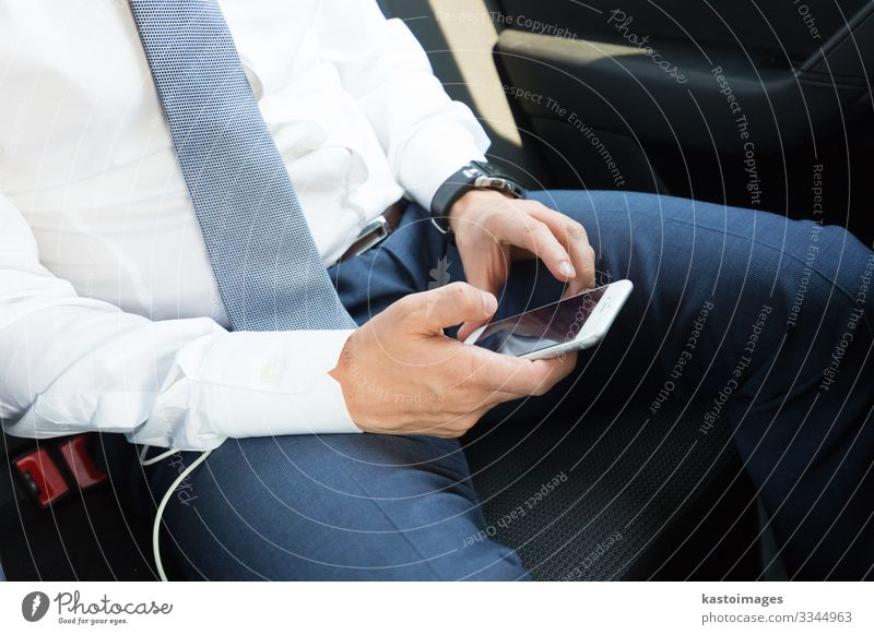 Close up of businessman using mobile smart phone in a car. Reading Decoration Work and employment Business Telephone PDA Screen Technology Internet Human being