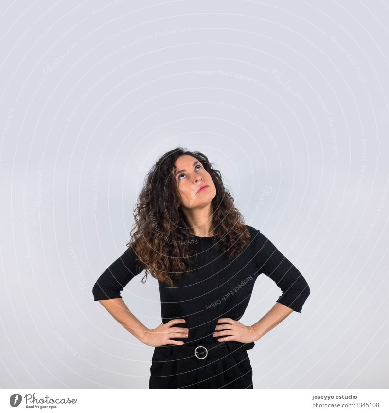 Curly haired brunette woman dressed in black with her hands on her waist looking up with thoughtful gesture. 30-40 years advertisement attitude background