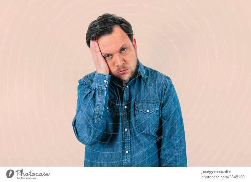 Young man with expression of extreme tiredness and sadness. Denim shirt and isolated pink background. 30-40 years advertisement advertising apathy attitude