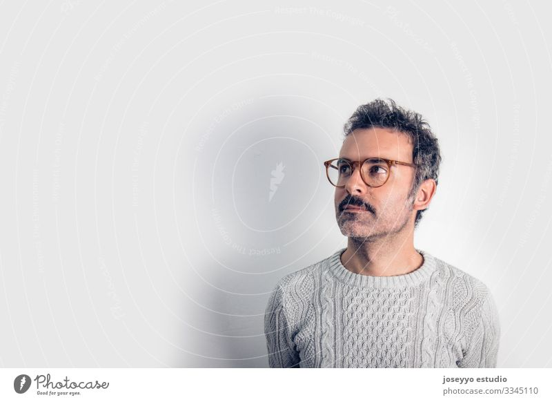 Portrait of  handsome and brown thinking man with mustache, glasses and  gray sweater. Gray background. Copy space adult arms attractive brain casual challenge